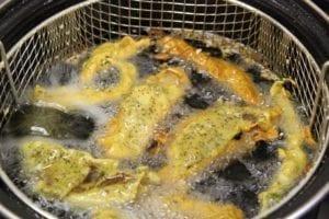 Frituren kan in een frituurpan (ja, hè-hè) of een fikse laag olie in een koekenpan of wok.